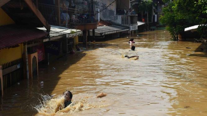 Sejumlah anak bermain air saat banjir melanda permukiman di kawasan Rawajati, Jakarta Selatan, Jum'at, 26 April 2019.