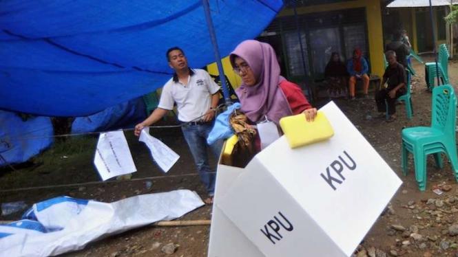 Petugas KPPS di Padang memindahkan bilik suara karena angin kencang dan hujan di Tabiang Banda Gadang, Padang, Sumatera Barat, Sabtu (27/4/2019). TPS di daerah tersebut rusak akibat angin kencang dan hujan sejak Sabtu pagi.
