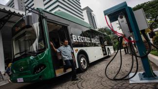 Penumpang turun dari bus listrik usai mengikuti uji coba di halaman Balai Kota Jakarta.