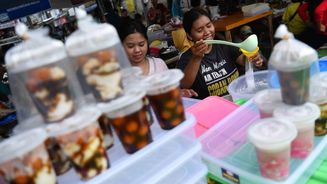 Pedagang membungkus minuman untuk dijual di Pasar Takjil Benhil, Jakarta, Senin, 6 Mei 2019.