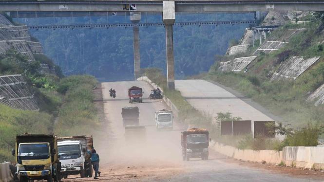 Sejumlah truk melintasi proyek pembangunan Jalan Tol Cileunyi-Sumedang-Dawuan (Cisumdawu) di Kabupaten Sumedang, Jawa Barat, Rabu, 8 Mei 2019.