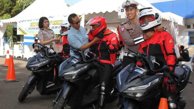 GM Corp.Comm. PT Astra Honda Motor Ahmad Muhibbuddin (Tengah) didampingi oleh Briptu Vanesha (Kiri) dari NTMC Polri dan Bripka Malvinas (Kanan) dari Korlantas melakukan penyematan helm ke para peserta acara Safety Riding Camp 2019.