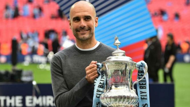 Manajer Manchester City, Pep Guardiola, bersama trofi Piala FA