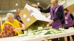 A man tips a big cardboard box full of green ballot papers onto a table as a woman watches on.