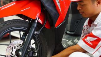 Teknisi mengecek rem sepeda motor