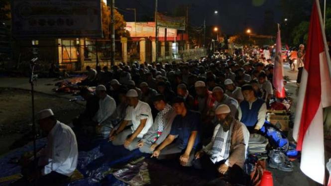 Massa menggelar salat Magrib berjamaah di depan Kantor KPU Sumut di Medan.