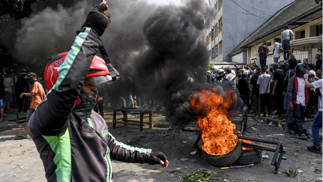 Massa membakar ban saat kerusuhan terjadi di Jalan Jati Baru Raya, Tanah Abang, Jakarta, Rabu 22 Mei 2019.