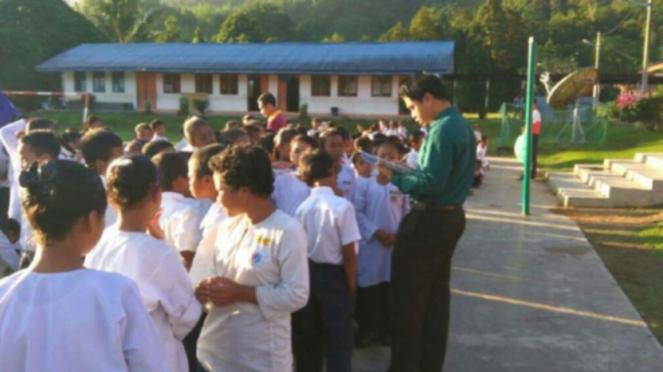 Ahmad Saidin Mohd Idris menuju sekolah tempatnya mengajar