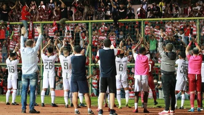 Pemain Madura United merayakan kemenangan bersama suporter