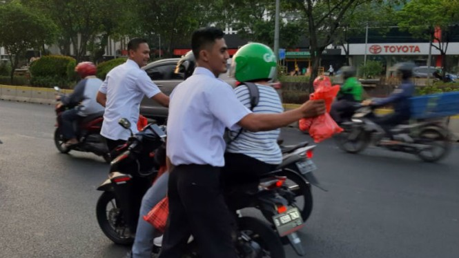 Petugas Ditjen PAS membagikan makanan berbuka untuk pengendara