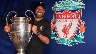 Manajer Liverpool, Juergen Klopp, memegang trofi Liga Champions