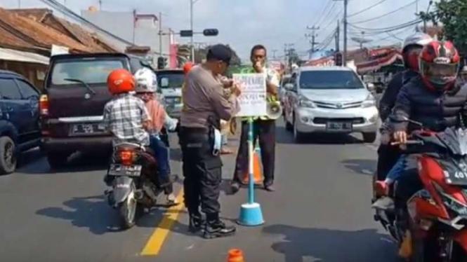 Polisi membuat papan petunjuk arah di pertigaan Cisaga, Ciamis, Jawa Barat