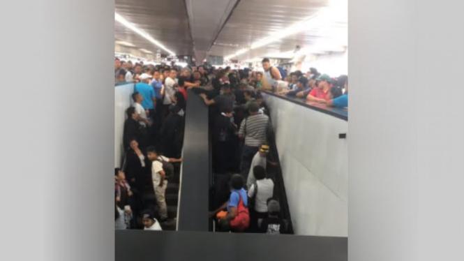 Orang membeludak di sebuah stasiun.