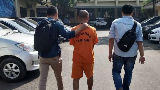 Hamdani, tersangka penistaan agama dan makar, saat akan diperiksa kejiwaannya dan dikawal dua penyidik Polres Garut, Jumat, 21 Juni 2019.