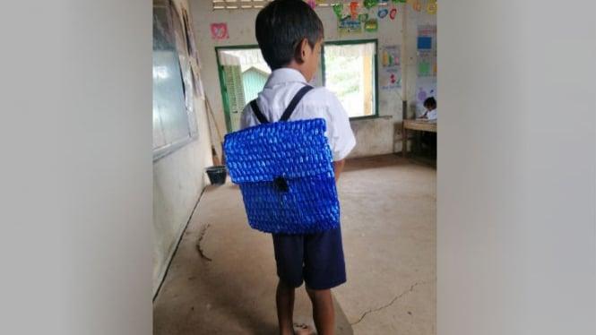 Ayah buatkan tas sekolah untuk anaknya.