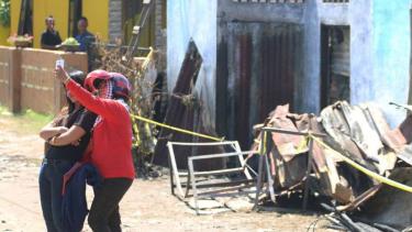 Dua wanita berswafoto dengan latar belakang bangunan pabrik korek api gas (mancis) yang hangus terbakar, di Desa Sambirejo, Langkat, Sumatera Utara, Minggu, 23 Juni 2019.