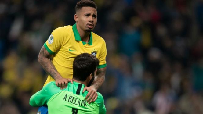 Striker Brasil, Gabriel Jesus, melakukan selebrasi bersama Alisson Becker
