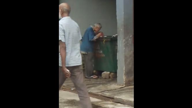 Kakek tua mengais makanan di tong sampah