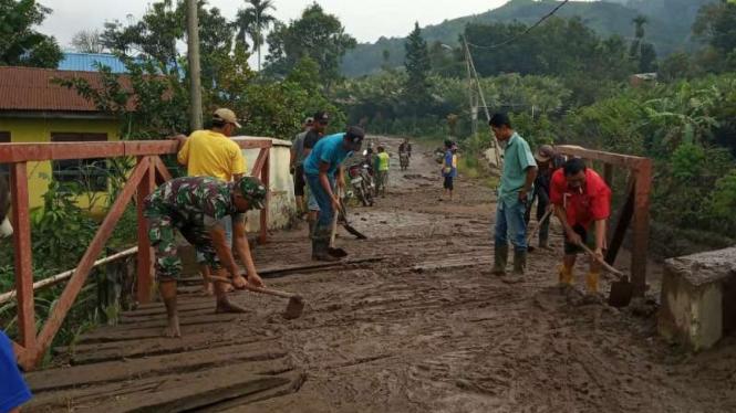 Aparat gabungan bergotong royong membersihkan material lahar dingin dari Gunung Sinabung di sejumlah desa di Kabupaten Karo, Sumatera Utara, Kamis, 11 Juli 2019.