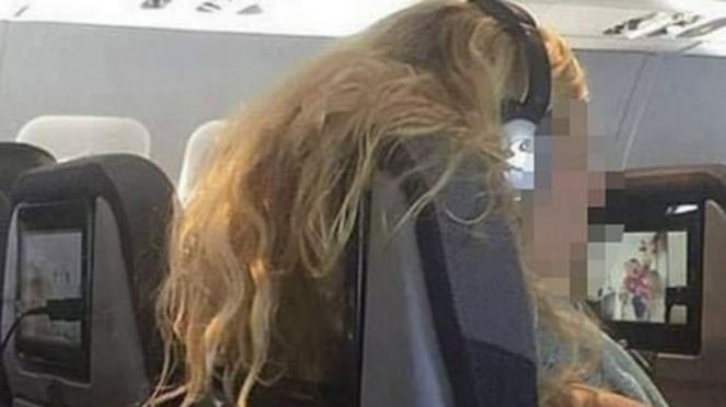 Penumpang wanita yang menyampirkan rambutnya ke belakang kursi