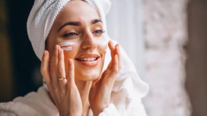 Ilustrasi wanita mengaplikasikan krim wajah