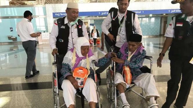 Mahmud (85) menggandeng tangan istrinya Mak Cum (75) di Bandara Madinah