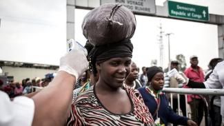 Seorang perempuan diperiksa suhu tubuhnya di pos pemeriksaan Ebola ketika dia memasuki Rwanda dari Kongo.-Getty Images