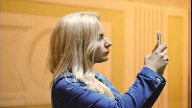 Seorang wanita mengecek ponsel