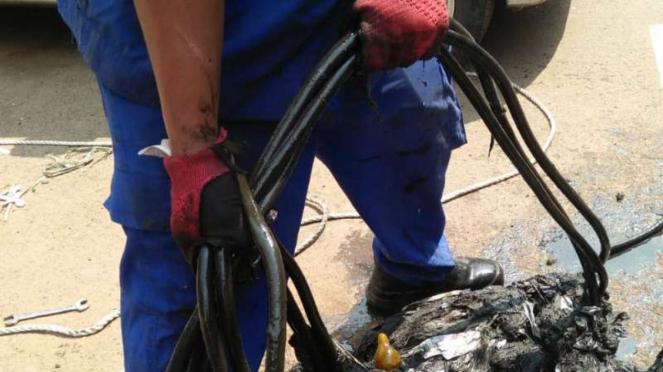 Petugas membersihkan sampah di gorong-gorong kawasan Mega Kuningan, Jakarta.