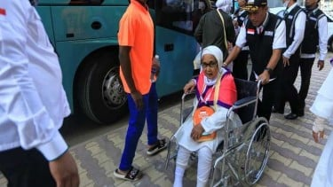 Jemaah haji lanjut usia didorong dengan kursi roda