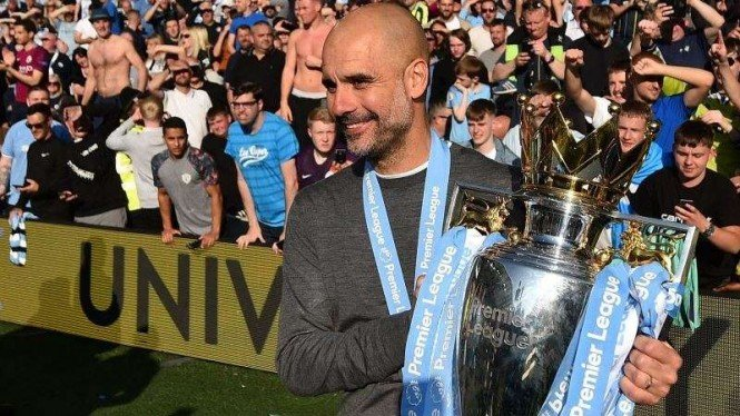 Manajer Manchester City, Pep Guardiola, memegang trofi Premier League