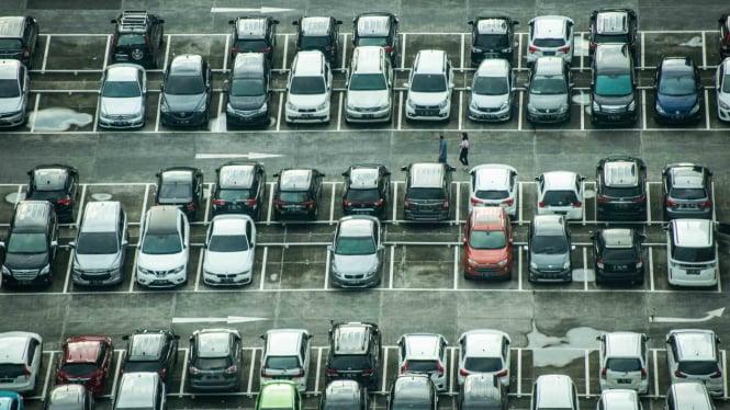 Warga berjalan di antara mobil yang terparkir di Jakarta.