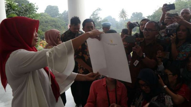 Baiq Nuril menunjukkan Keppres amnestinya kepada wartawan di Istana Bogor
