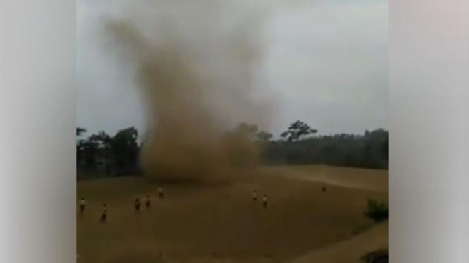 Anak-anak bermain di dekat angin puting beliung.