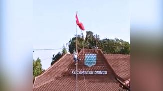 Yudha, siswa kelas XII MIPA 5 SMA Dringu, Kabupaten Probolinggo, Jawa Timur saat memanjat tiang bendera untuk membenahi Bendera Merah Putih yang nyangkut  saat Upacara Penurunan Bendera di kantor Kecamatan Dringu, Sabtu (17/8/2019) (FOTO: Istimewa)