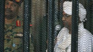 Omar al-Bashir muncul di pengadilan di balik sel pada hari Senin. - AFP.