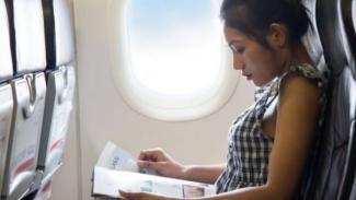 Wanita sedang membaca majalah di pesawat