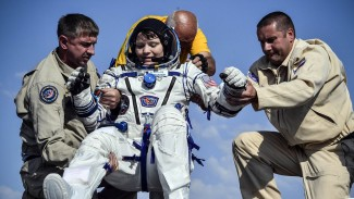 Anne McClain dibantu keluar dari kapsul ruang angkasa setelah kembali dari ISS bulan Juni lalu - Reuters.