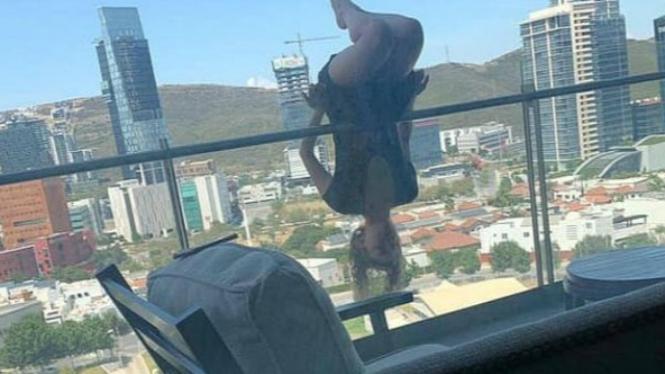 Pose yoga dari balkon.