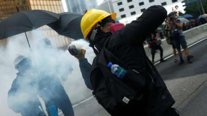 Seorang demonstran melempar tabung gas air mata ke arah polisi saat demonstrasi di Hong Kong pada hari Sabtu
