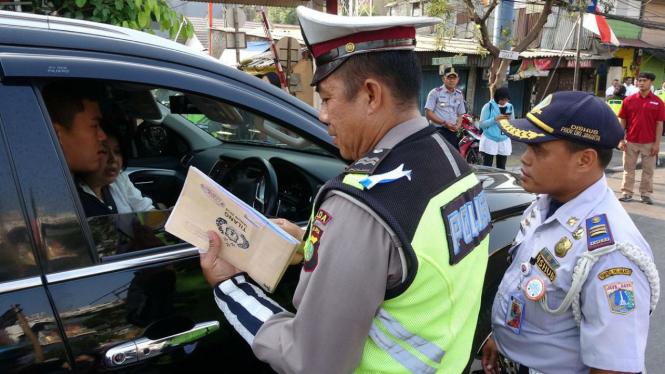 Ilustrasi polisi menindak pelanggar ganjil genap