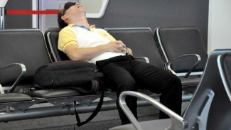 A traveller sleeps in Sydney Airport.