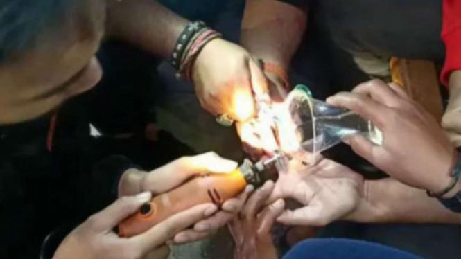 Petugas Damkar Depok memotong cincin dengan gerindra.