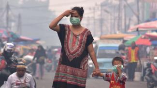 Seorang ibu dan anaknya mengenakan masker medis saat asap kebakaran hutan dan lahan (Karhutla) menyelimuti Kota Pekanbaru, Riau, Selasa (10/09). - ANTARA FOTO/FB Anggoro