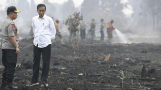 Presiden Joko Widodo (kanan) didampingi Kapolri Jenderal Pol Tito Karnavian meninjau penanganan kebakaran lahan di Desa Merbau, Kecamatan Bunut, Pelalawan, Riau, Selasa 17 September 2019