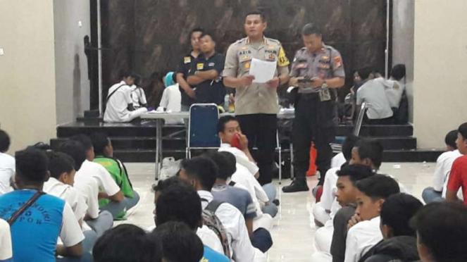 Polisi mengumpulkan puluhan pelajar asal Depok yang diamankan saat mereka hendak pergi berdemonstrasi ke Jakarta pada Senin, 30 September 2019.