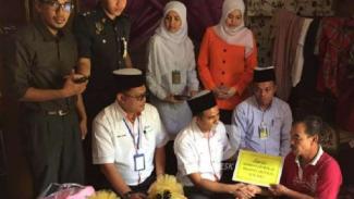 Mohd Zain Abdullah (paling kiri) ketika menerima bantuan.
