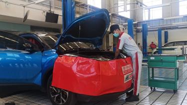 Teknisi sedang servis mobil Toyota C-HR Hybrid di bengkel Auto2000 Banyuwangi.