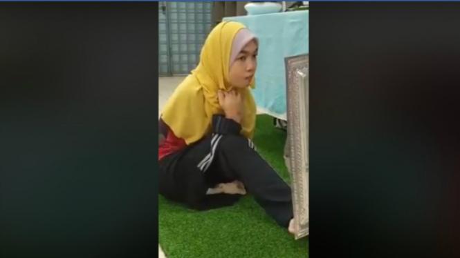 Gadis tanpa lengan tunjukkan cara pakai jilbab dengan kaki