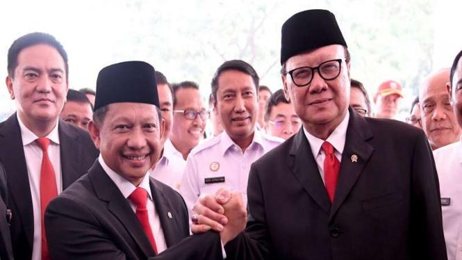 Menteri Dalam Negeri Tito Karnavian (kiri) berjabat tangan dengan pendahulunya, Tjahjo Kumolo.